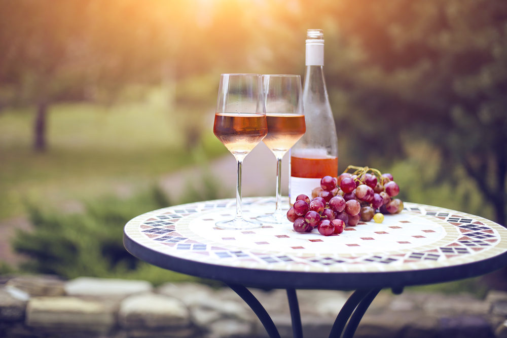 Two glasses and bottle of rose wine in autumn vineyard on marble