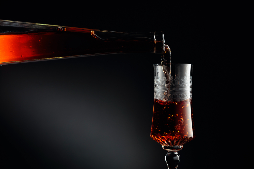 Aged golden fortified wine from the antique bottle being poured